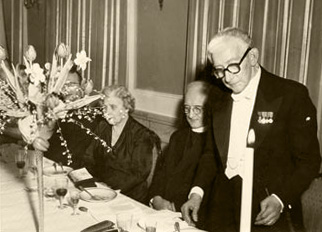 Gammal, svartvit bild av högtidsklädda personer vid ett dukat bord.