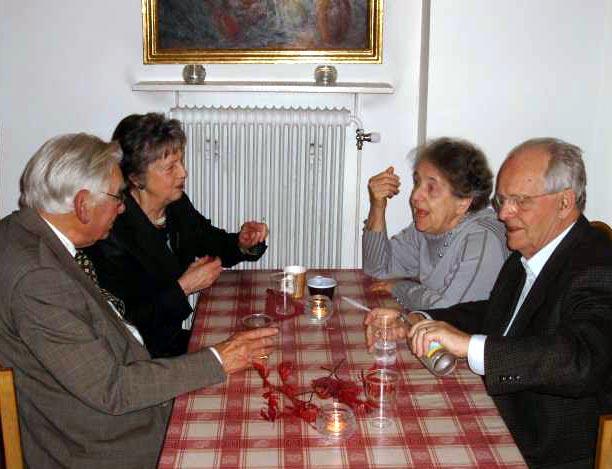 Fyra av föreningens medlemmar i glatt samspråk kring ett bord.